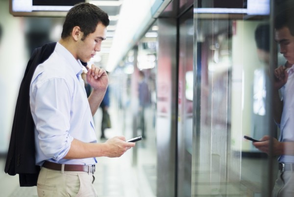 Businessman looking at his phone and waiting for subway